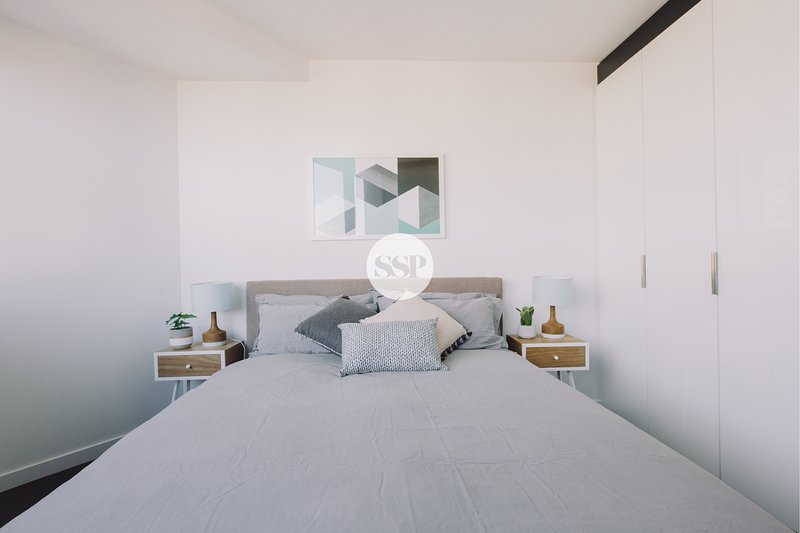 The master bedroom with a queen sized bed & plush pillows.