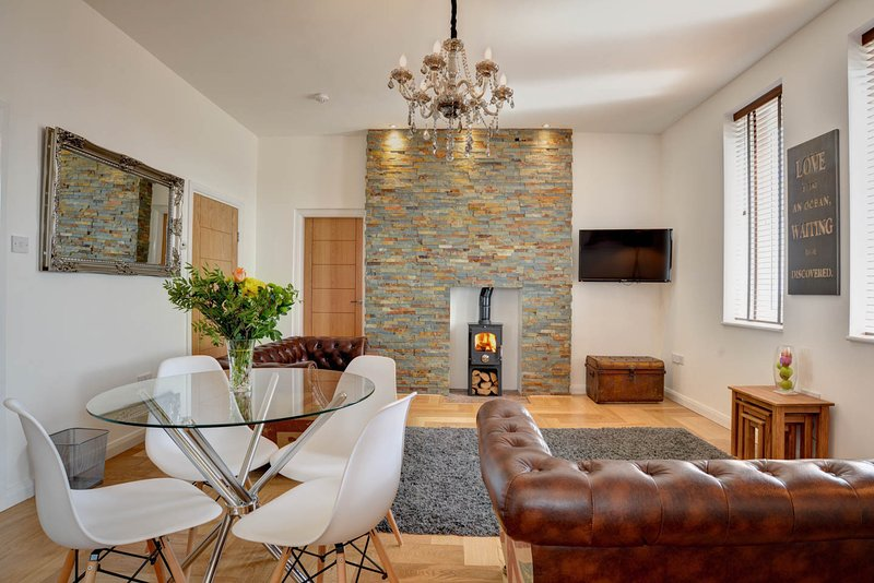Lounge with log burner, oak floors, slate feature wall wall and crystal chandelier.