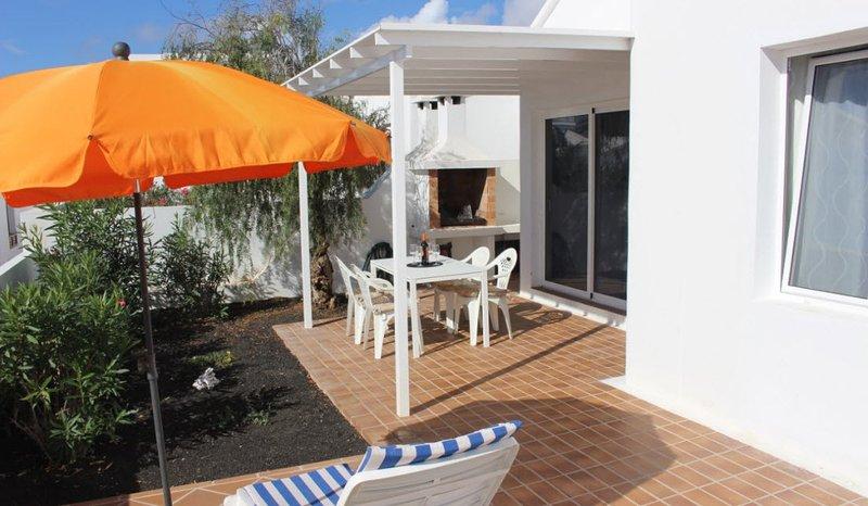 Vilsam bakre terrass med grill, enkel villa åtkomst via skjutdörrar.