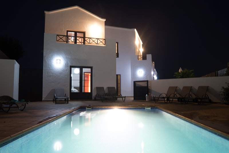 The villa and pool lit at night