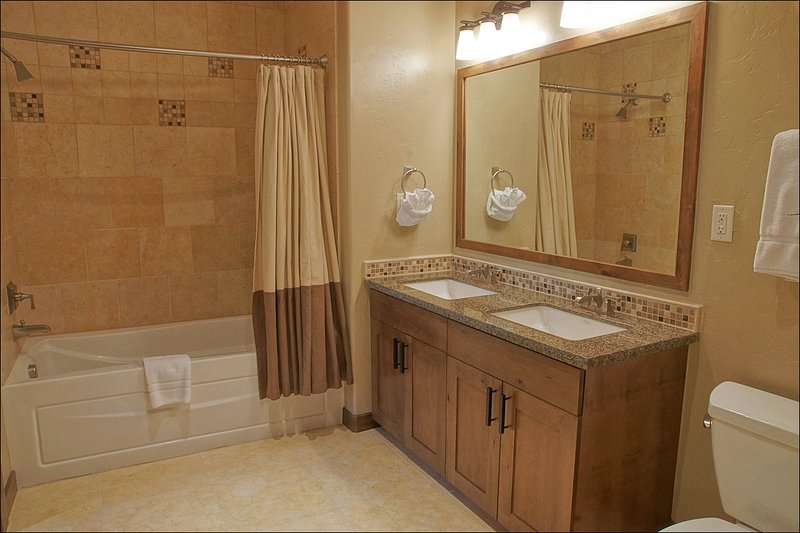The bathroom features a large tub and dual sink vanity