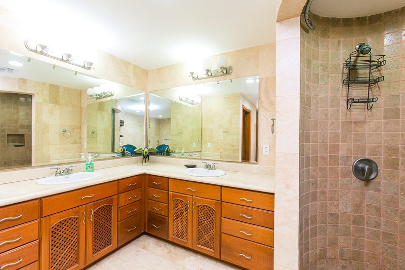 The bathroom has a walk-in shower and double vanities