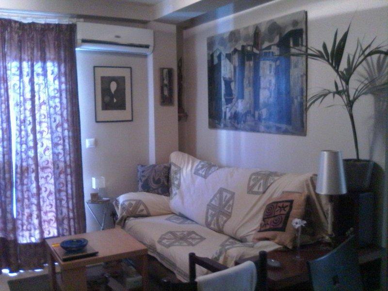 Sala de estar con sofá tres plazas, butaca y A/A.