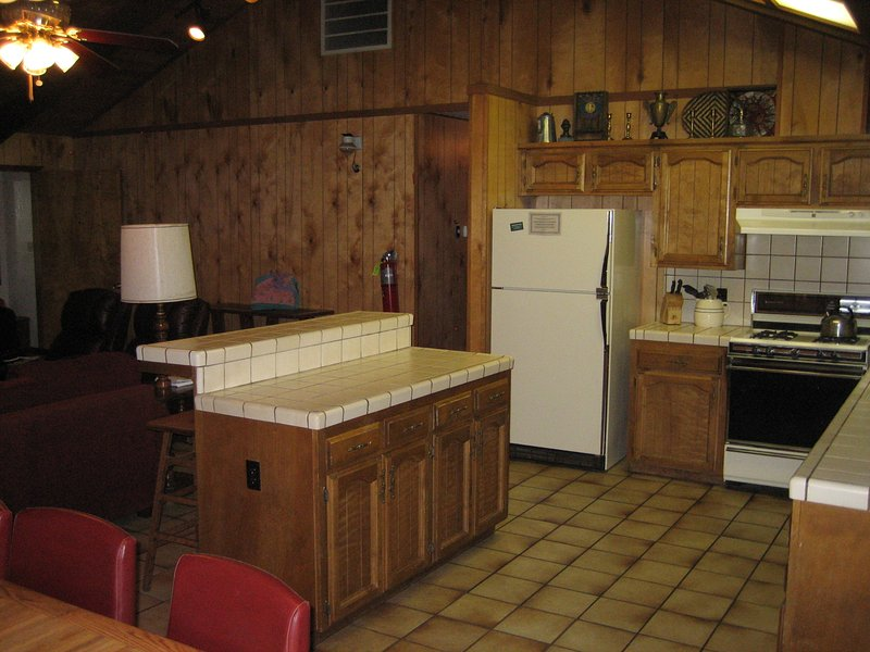 Spacious kitchen with island/counter with 3 stools.