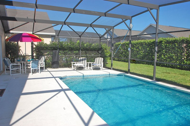 Pool with patio table, umbrella and loungers