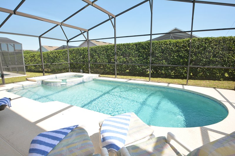 Pool and sun loungers with privacy hedge