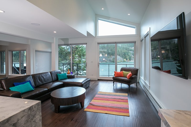 large open plan living area with deck and views of the lake