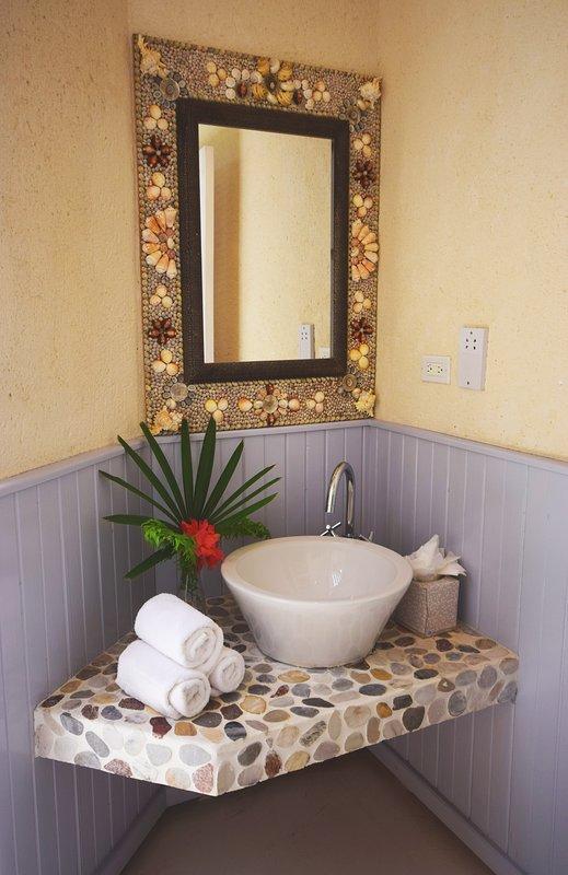 La bella vanità di conchiglie e pietre nel bagno padronale en-suite