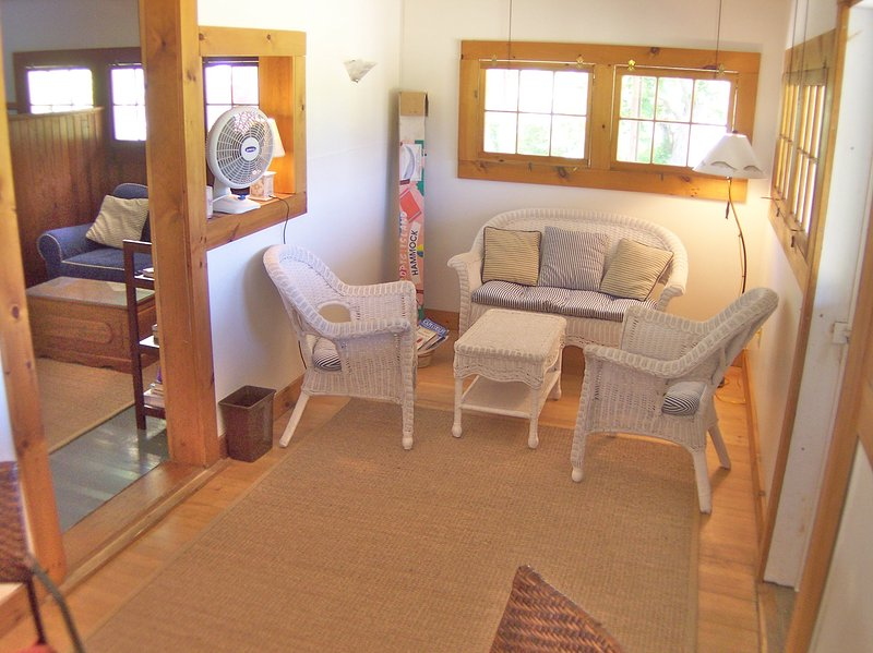 Inside, there are two living areas, this area used to be a porch, but now is enclosed with a seating area and a small table