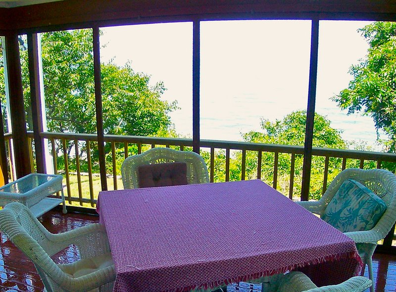 The screened porch overlooking the beach and bay provides stunning views for breakfast, lunch and dinner.