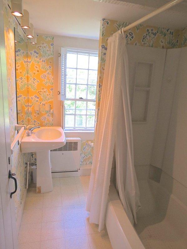 Este baño completo de nivel superior tiene una combinación de bañera / ducha