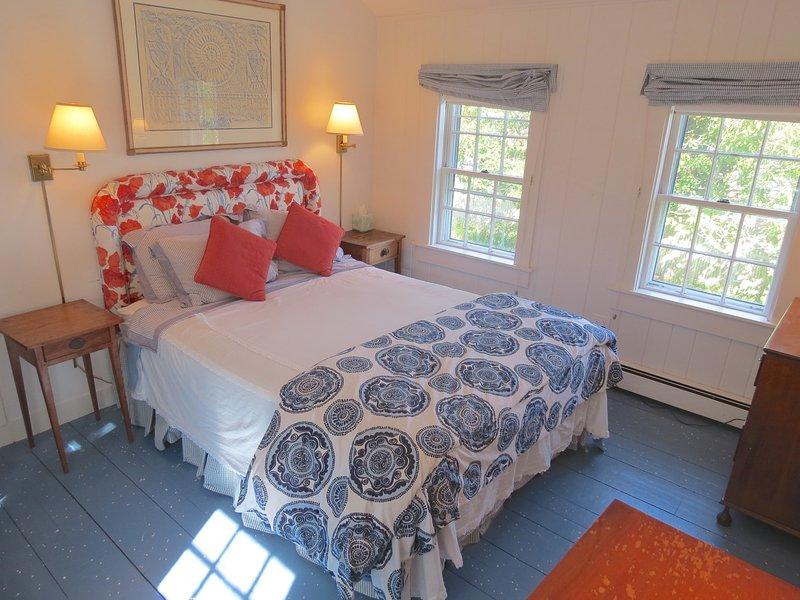 El dormitorio principal de arriba tiene una cama de matrimonio y techos abovedados