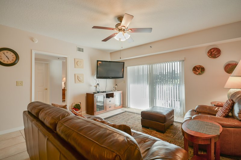 Beautifully decorated living room with flat screen TV, DVD, cozy recliner and sliders to the balcony.