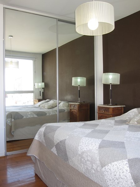 Master room has a king-size bed, floor-to-ceiling mirror closets and design bedside lamps and tables