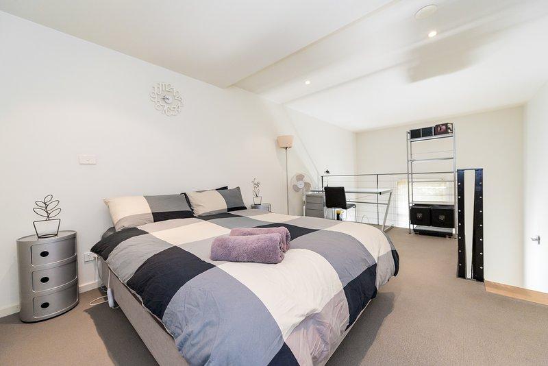 Une chambre ouverte avec un lit queen, bureau et salle de bains.