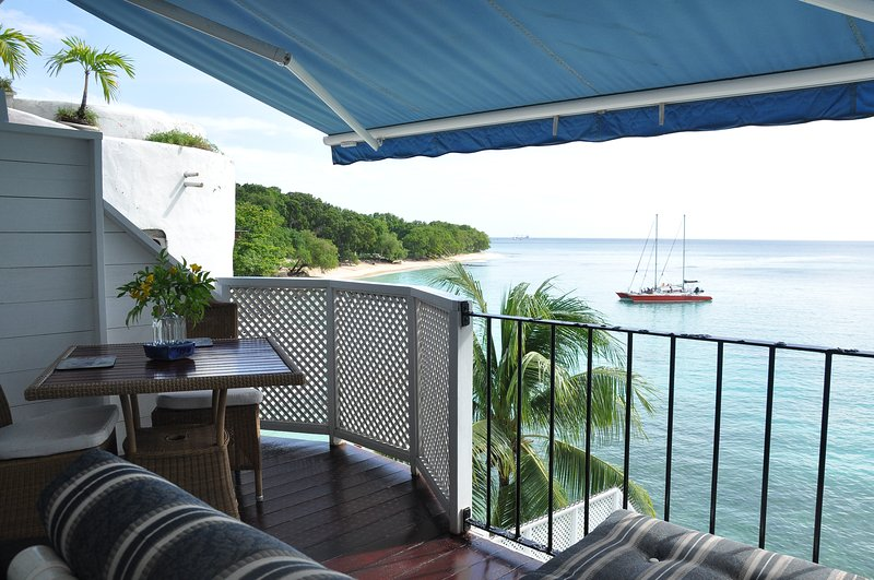 view from Upper studio private balcony,with alfresco dining, two loungers and awning extended