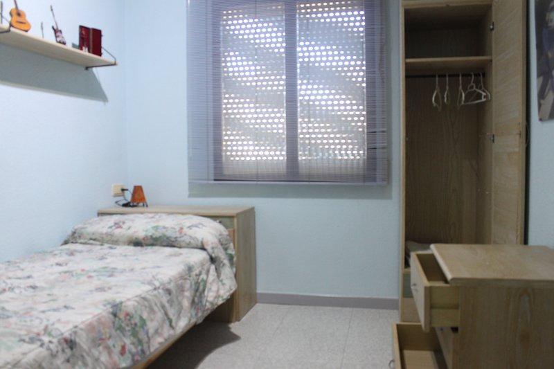 Habitación independiente con cama individuale, salón cocina y baño compartidos.
