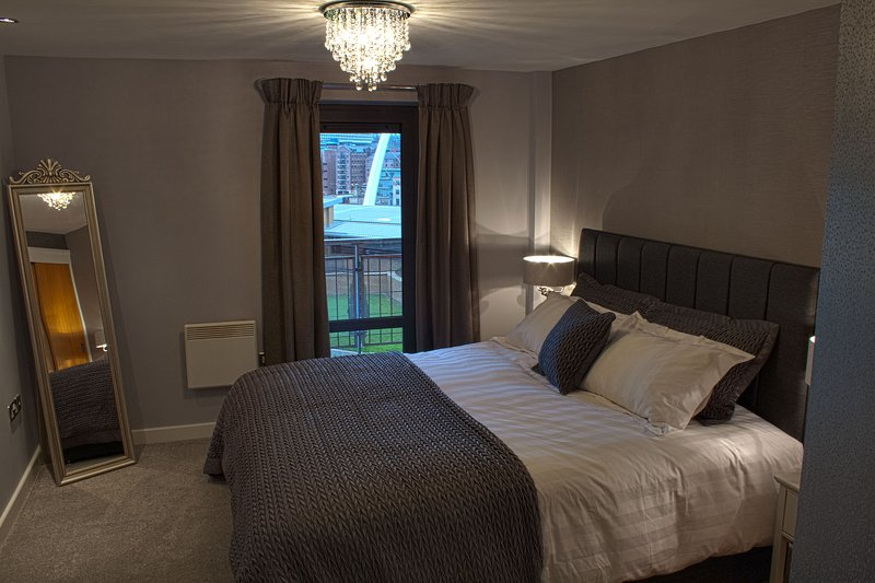 Bedroom area with balcony access and views of River Tyne and Millennium Bridge.