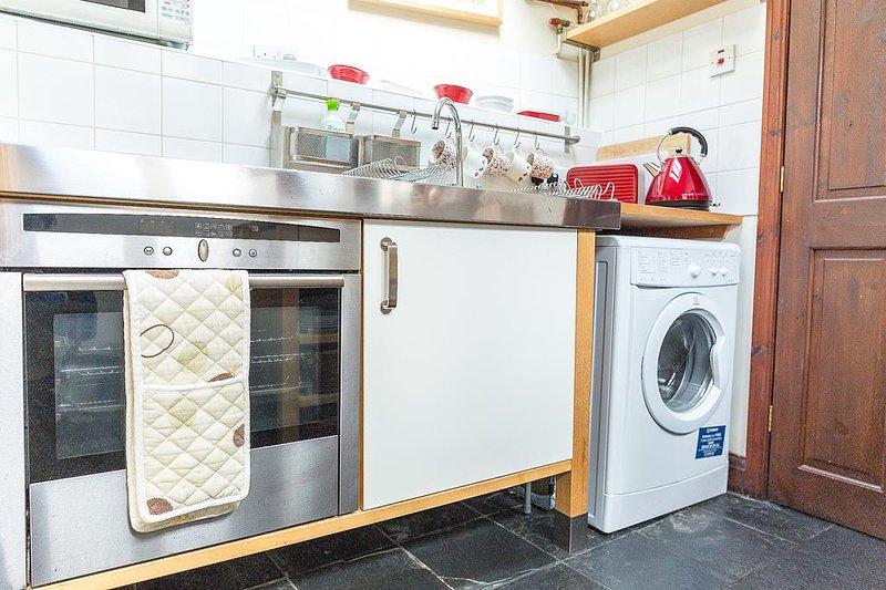 The kitchen - oven, hob, microwave, fridge, washing machine