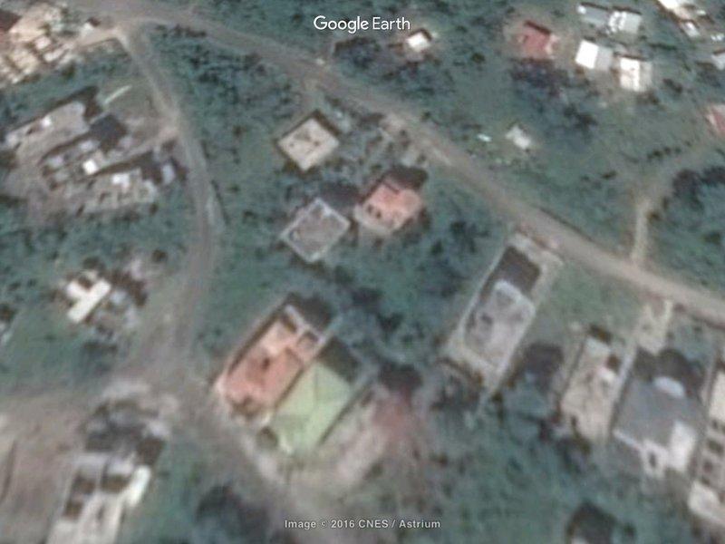 Happy Villa, casa sin terminar en la parte posterior media de 3 edificios en la parte delantera de la imagen