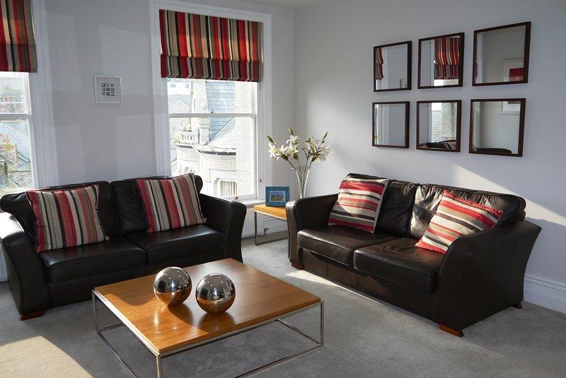Salón con sofá de cuero y sofá cama