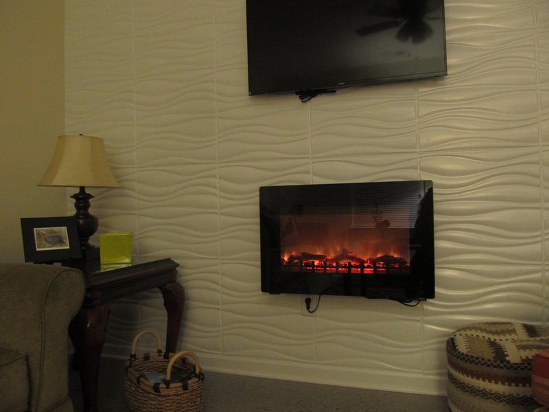 Accent wall in the living room with the tv and electric fireplace/heater.