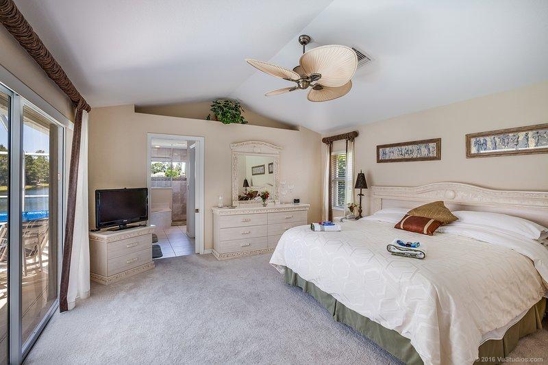 El dormitorio principal con cama de matrimonio con vistas a la piscina.