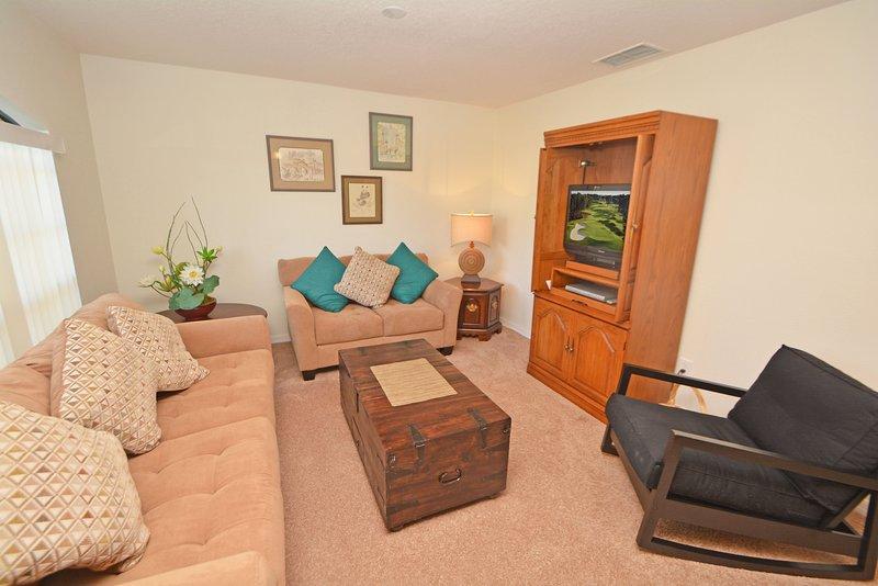 Formele zithoek met comfortabele stoelen en een flatscreen TV & DVD