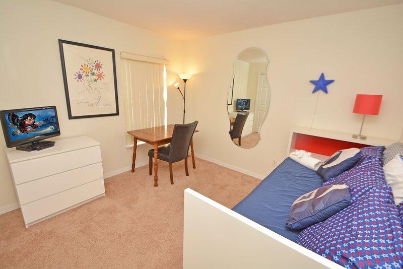 Slaapkamer 5 heeft dag bed met uitschuifbaar eronder, een bureau en een flatscreen TV & DVD