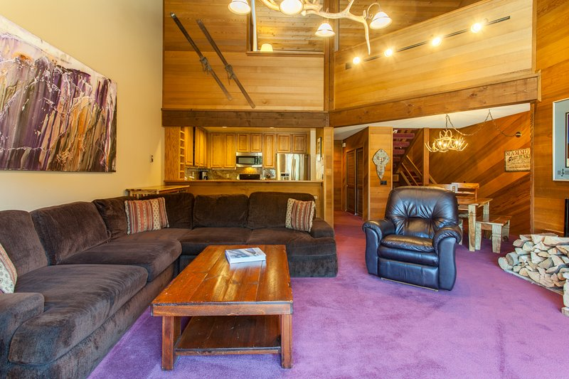 Living Room - sectional couch, two arm-chairs, wood burning fireplace and flat-screen TV/DVD player, deck with wood and barbecue