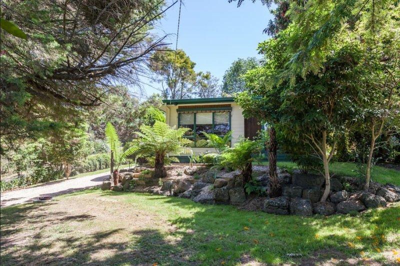 jardins rocheux paysagers entourent la maison individuelle. arbres établis fournissent de l'ombre.