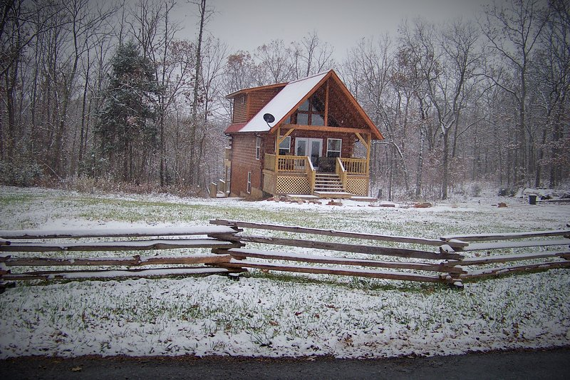 Snow falling on Ellen's log cabin