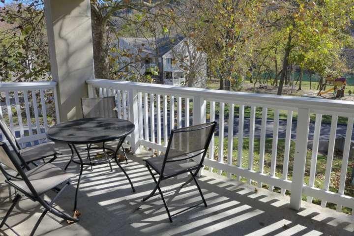 Deck privado cubierto con mesa para cuatro personas, con vistas al patio y el lago Taneycomo.