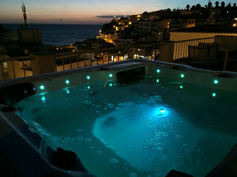 The rooftop hot tub by night overlooking the town square & sea
