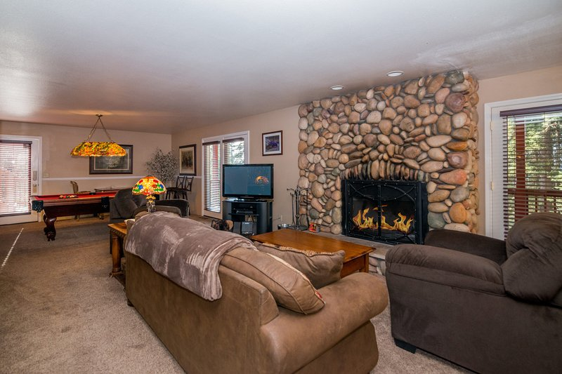 Your living area with wood-burning fireplace, queen sofa sleeper, HD satellite TV and pool table.