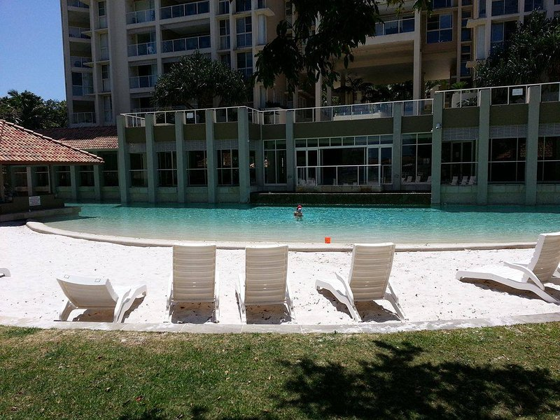 playa de arena junto a la piscina