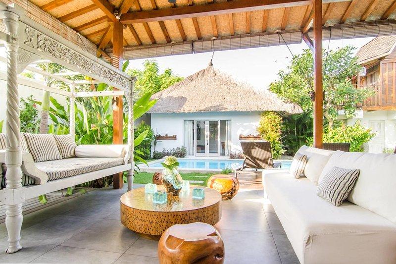 Méridienne et un canapé dans le salon avec vue sur la chambre principale de la piscine