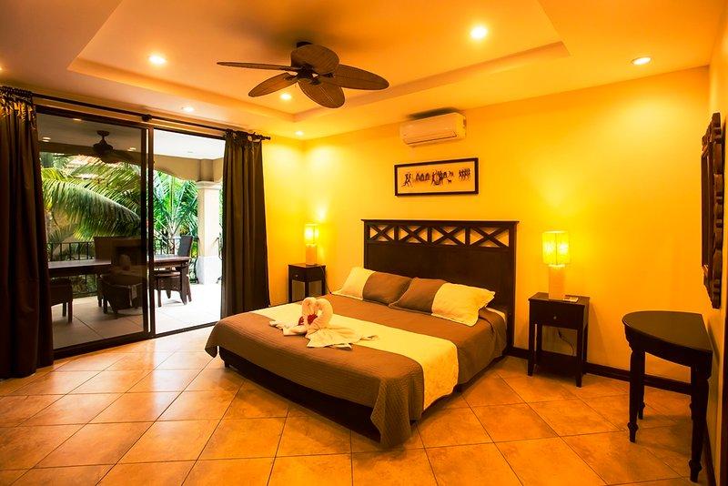 dormitorio principal con cama doble, baño privado y balcón con jardín y vista parcial de la montaña.