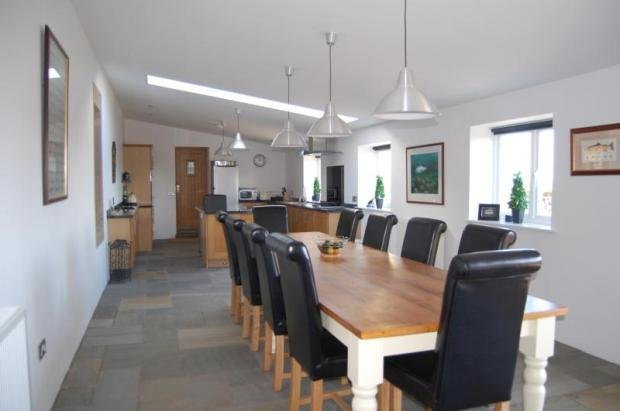 large kitchen table seats up to 16 people , large tv on wall