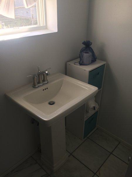 Pristine douche carrelage personnalisé, lavabo piédestal, serviettes et laveuse / sécheuse