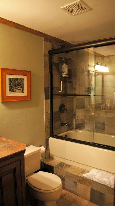 El baño completo tiene un fregadero hundido cobre, WC, bañera, ducha sobre la bañera y calefacción por suelo radiante.