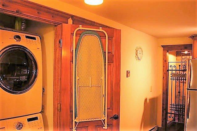 La lavandería está en la cocina con una lavadora de alta final y secadora y sus necesidades de planchado.