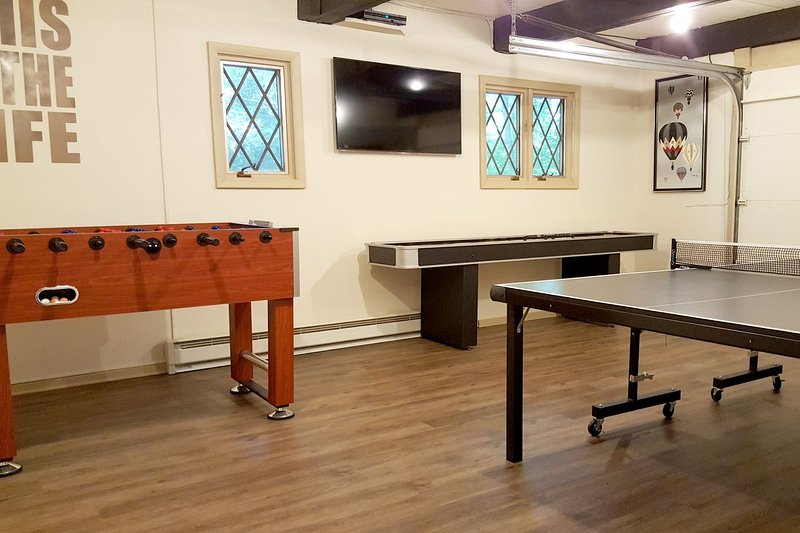 The game room with ping pong table, foosball, shuffle board table electronic darts & 55' TV