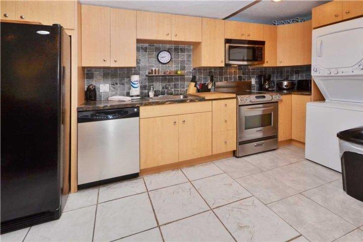 Belle cuisine rénovée avec grand réfrigérateur, lave-vaisselle, four et micro-ondes