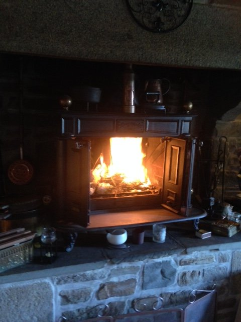 Large wood burner in a granite fireplace for chilly evenings.
