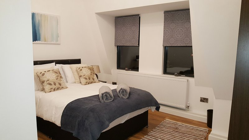 El primer dormitorio, decorado con cojines de colores y una alfombra.
