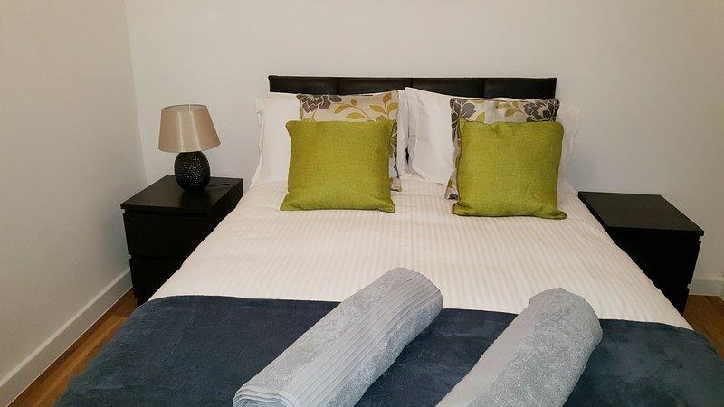Um dos dois quartos com uma cama de casal confortável.