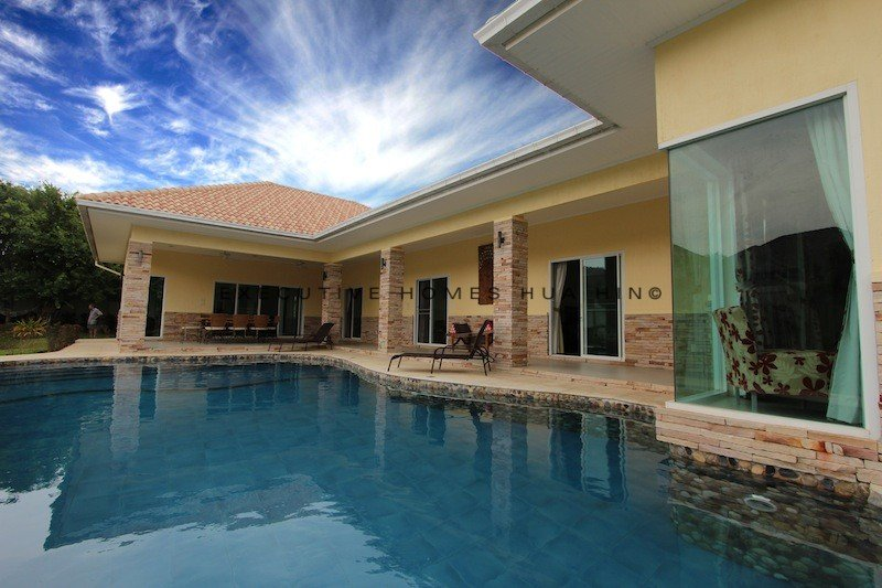 Lagoon style swimming pool with blue marble sides with Jacuzzi seating area.