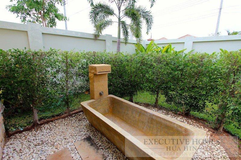 Piedra baño exterior cascada. agua caliente y fría. En el área de jardín privado