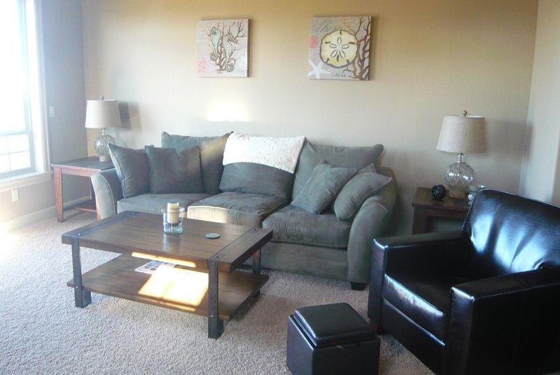 Ampio soggiorno con divano di grandi dimensioni ed accoglienti sedie in pelle. Deck ha vista grande, barbecue, posti a sedere
